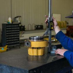 Employee measuring a hydraulic cylinder